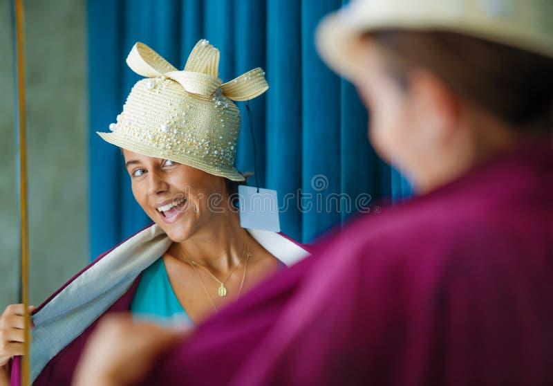 享受购物的年轻美丽和愉快的妇女试验衣裳和看在秀丽时尚商店smi的葡萄酒帽子镜子 免版税图库摄影