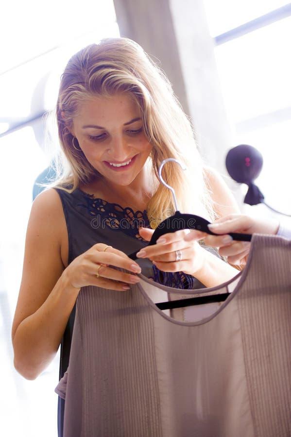享受购物的年轻美丽和愉快的白肤金发的妇女坦率的生活方式画象试验甜礼服在葡萄酒和冷却是 免版税库存图片
