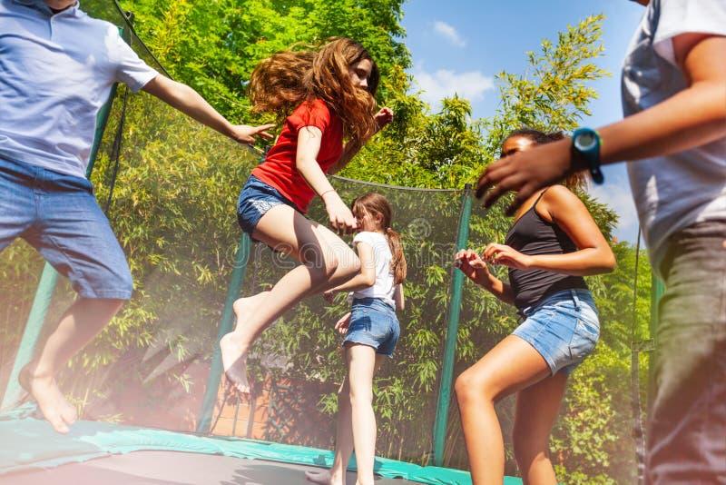 享受跳跃在绷床的男孩和女孩 免版税库存照片