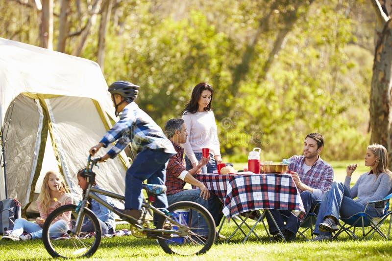 享受野营假日的两个家庭在乡下 免版税库存图片