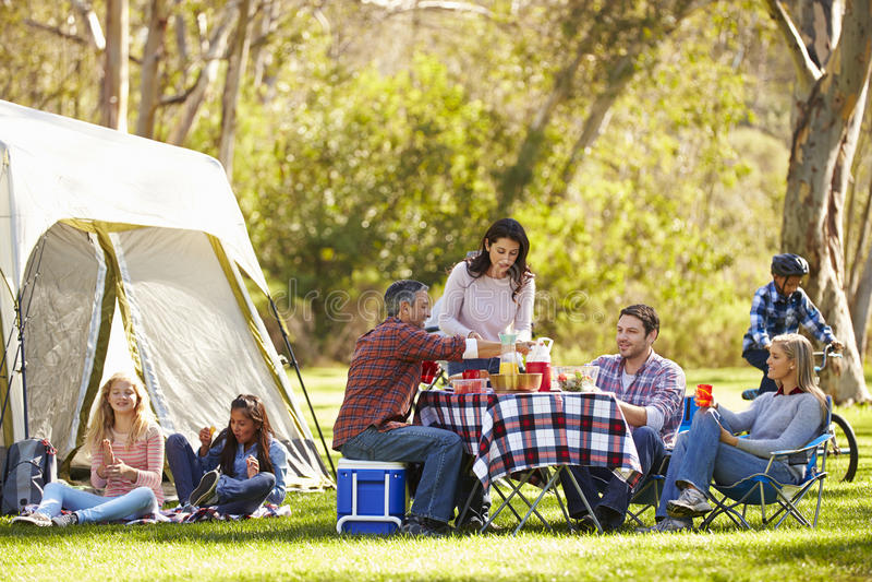 享受野营假日的两个家庭在乡下 库存图片