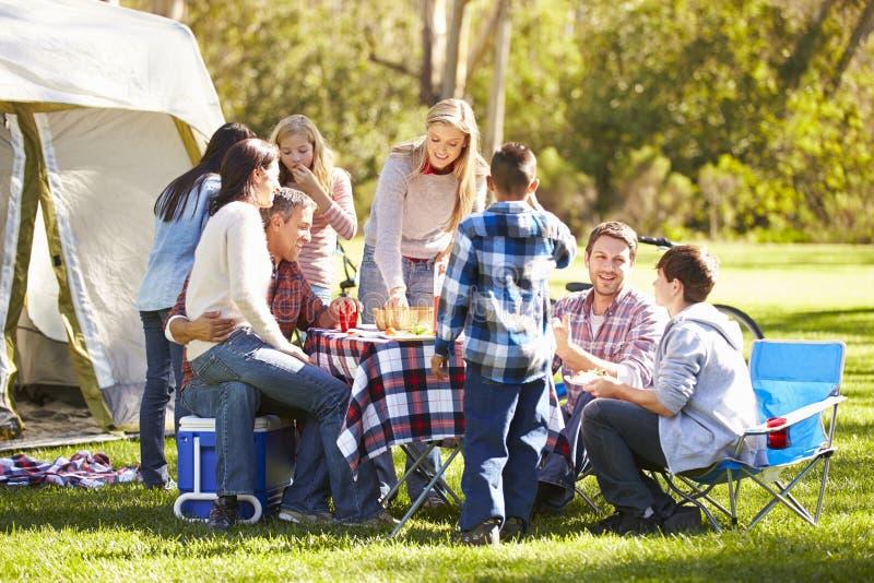 享受野营假日的两个家庭在乡下 库存照片