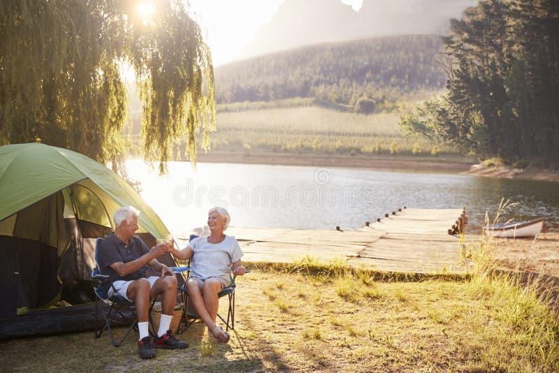 享受野营的假期的资深夫妇由做多士的湖 库存照片