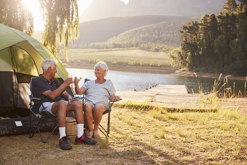 享受野营的假期的资深夫妇由做多士的湖 库存图片
