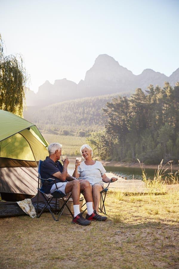 享受野营的假期的资深夫妇由做多士的湖 免版税库存照片