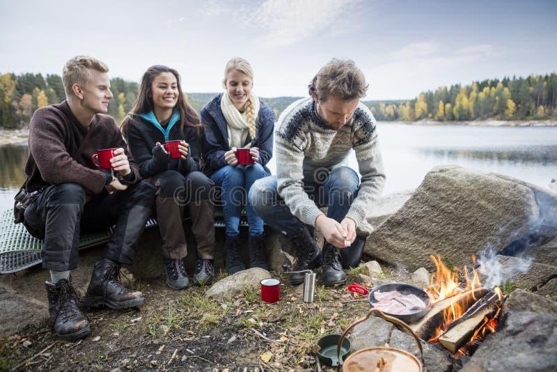 享受野营的年轻朋友湖岸 免版税库存图片