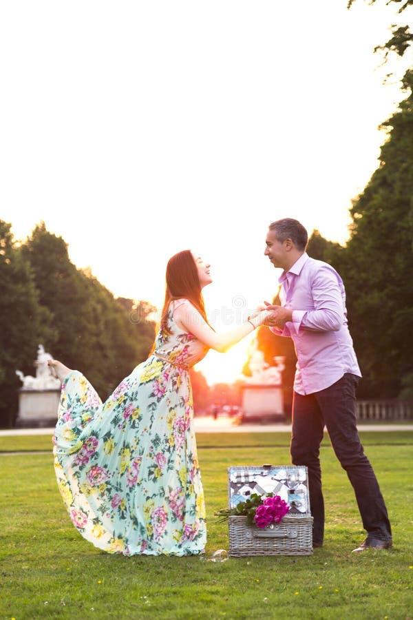 享受野餐时间的典雅的夫妇在晴朗的公园 免版税图库摄影