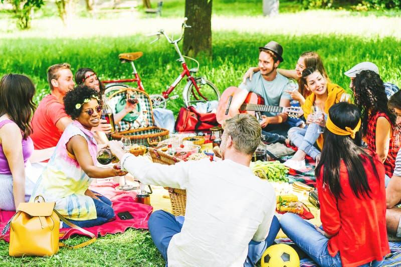 享受野餐的小组朋友,当吃和喝红酒坐毯子在室外时的公园 免版税库存图片