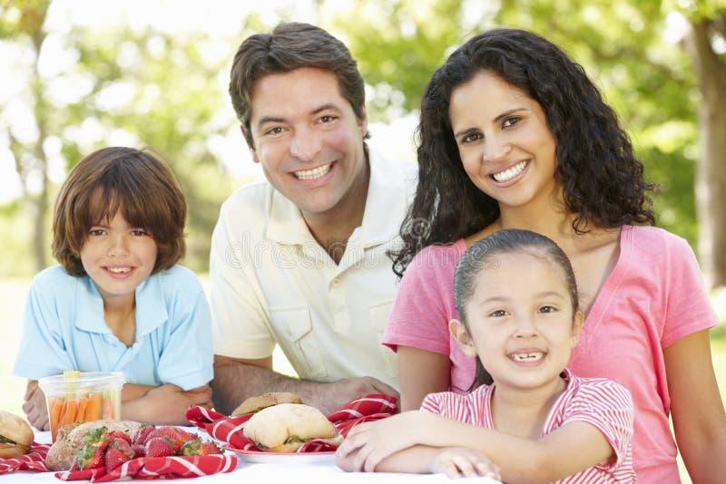 享受野餐的年轻西班牙家庭在公园 免版税库存照片