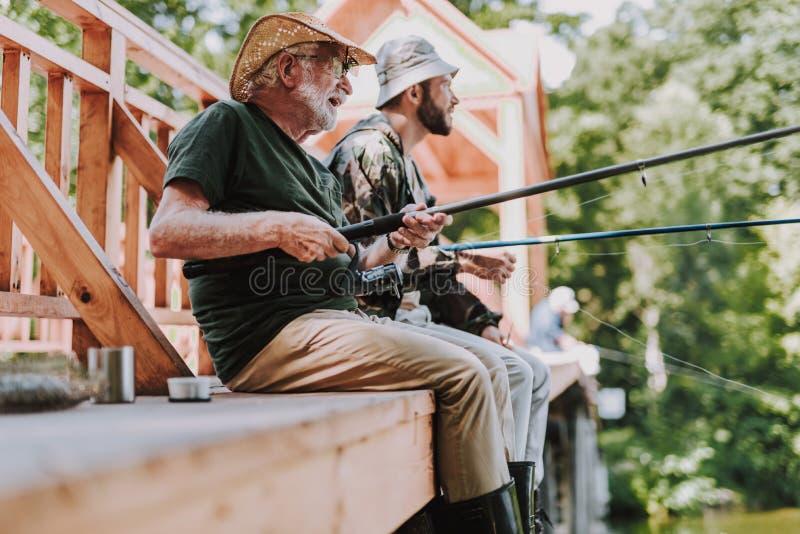 享受钓鱼与他的儿子的正面年迈的人 图库摄影