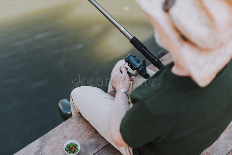 享受钓鱼的一个年迈的人的顶视图 库存照片
