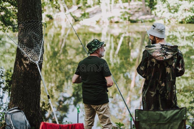 享受钓鱼的正面钓鱼者背面图  图库摄影
