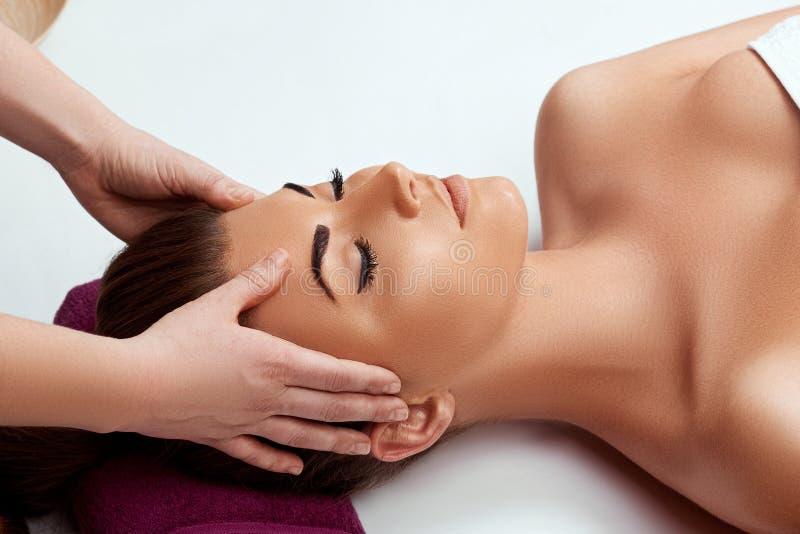 享受防皱面部按摩的年轻美女 做顶头按摩的男性治疗师对女性客户 免版税图库摄影