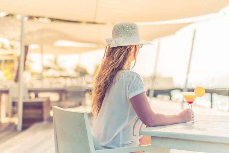 享受阳光和喝在海滩的美丽的无忧无虑的妇女画象鸡尾酒 夏天海滩背景概念 免版税库存图片