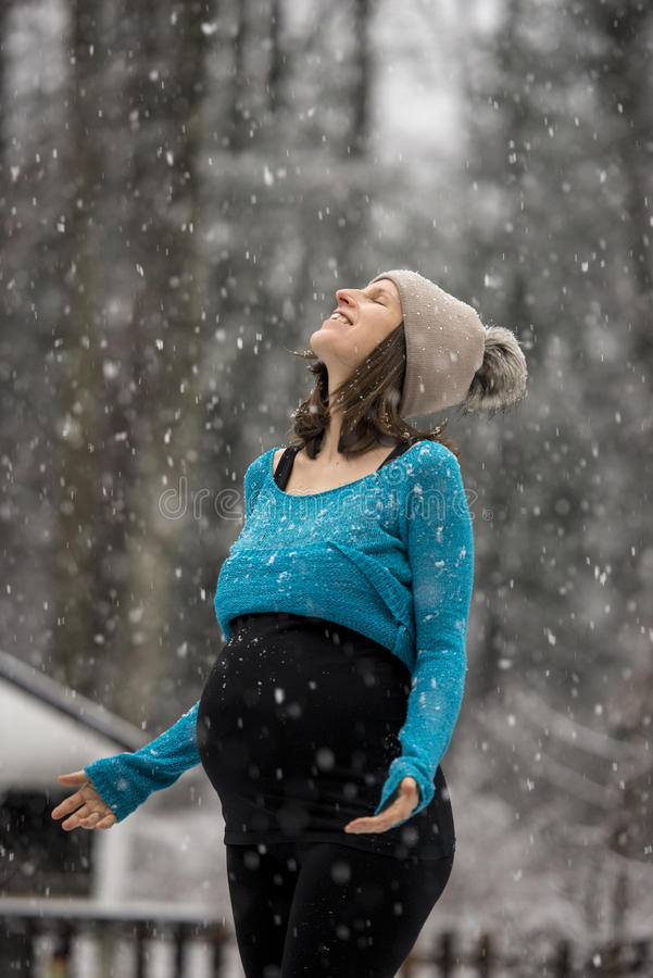 享受降雪的孕妇 库存照片