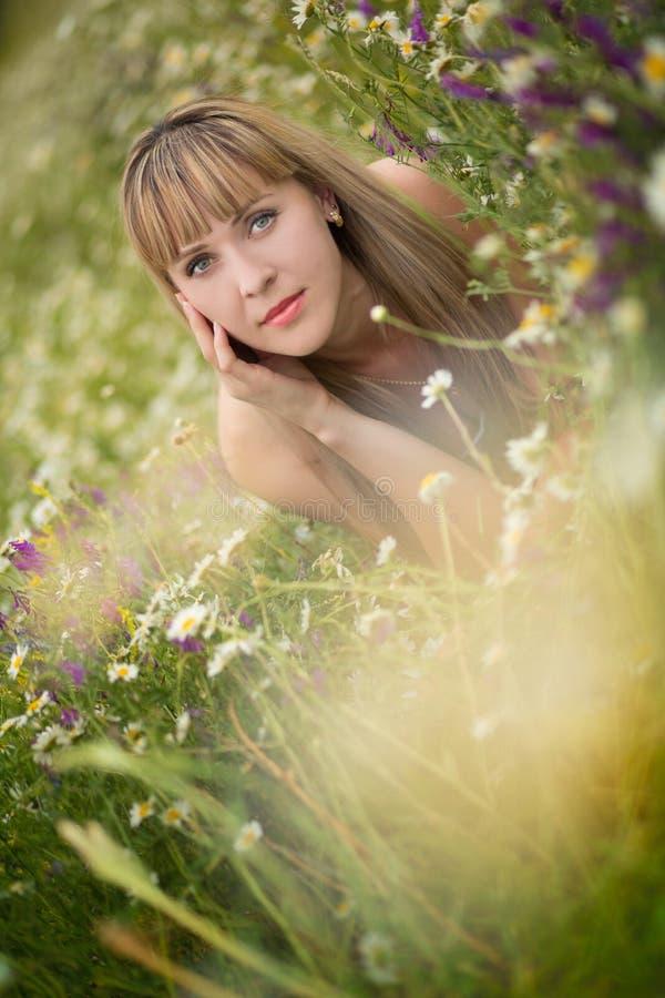 享受雏菊领域,好女性的美丽的妇女躺下在花草甸,俏丽女孩放松室外,获得乐趣, holdi 免版税库存照片