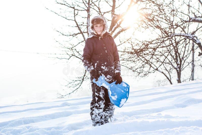 享受雪橇乘驾的小男孩 ??sledding 乘坐爬犁的小孩孩子 在雪儿童游戏户外 在的孩子雪撬 免版税库存照片