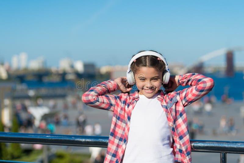 享受音乐到处 该当a听的最佳的音乐应用程序 女孩孩子听音乐户外与现代耳机 库存图片