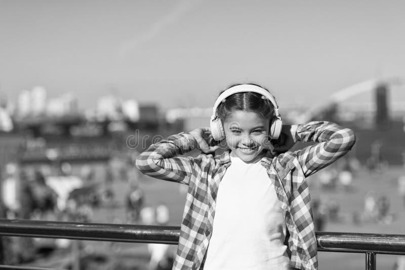 享受音乐到处 该当a听的最佳的音乐应用程序 女孩孩子听音乐户外与现代耳机 库存照片
