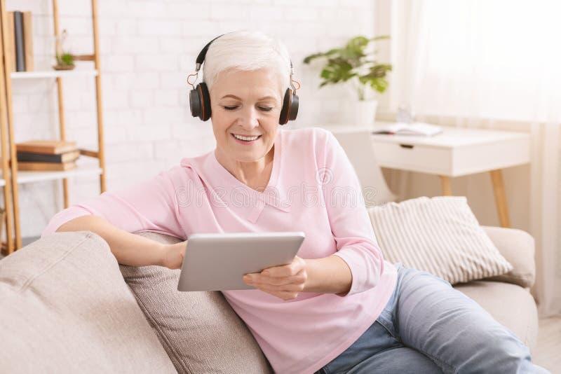 享受音乐和观看在平板电脑的资深妇女录影 免版税库存照片