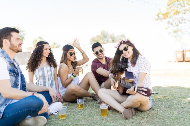 享受音乐和饮料在节日的朋友 库存照片