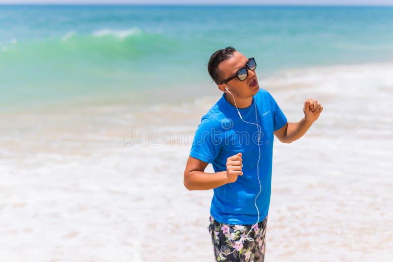 享受音乐炫耀耳机的生活方式愉快的年轻人走在海岸的 免版税库存图片