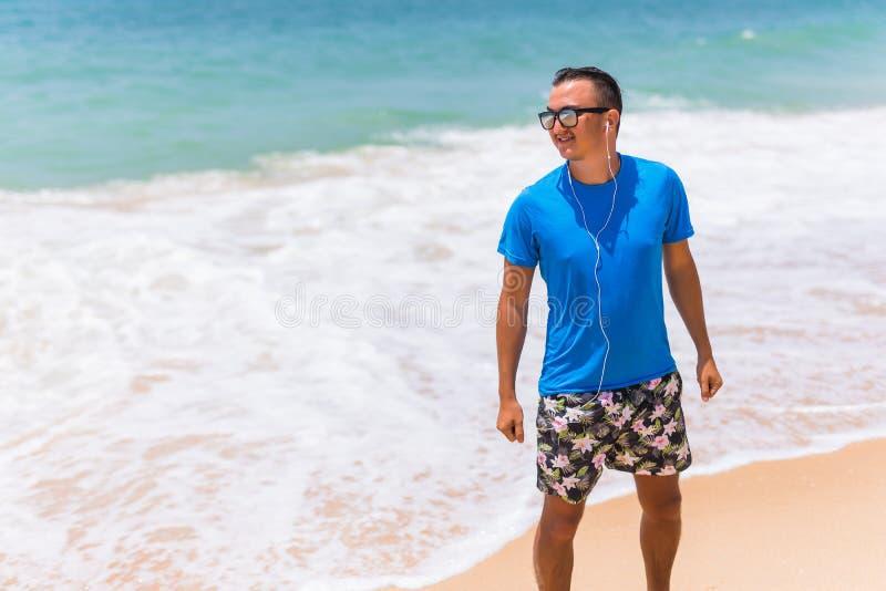 享受音乐炫耀耳机的生活方式愉快的年轻人走在海岸的 图库摄影