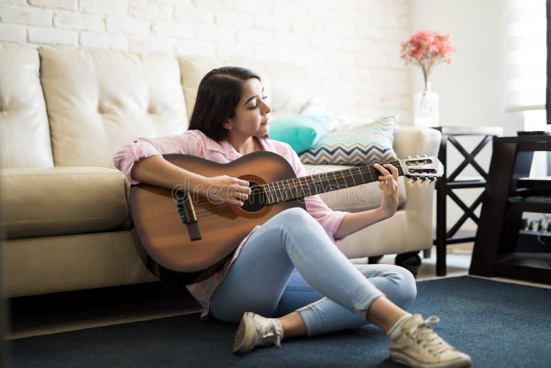 享受音乐的妇女通过弹吉他 免版税库存图片