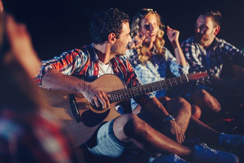 享受音乐的朋友在营火附近在晚上 库存图片