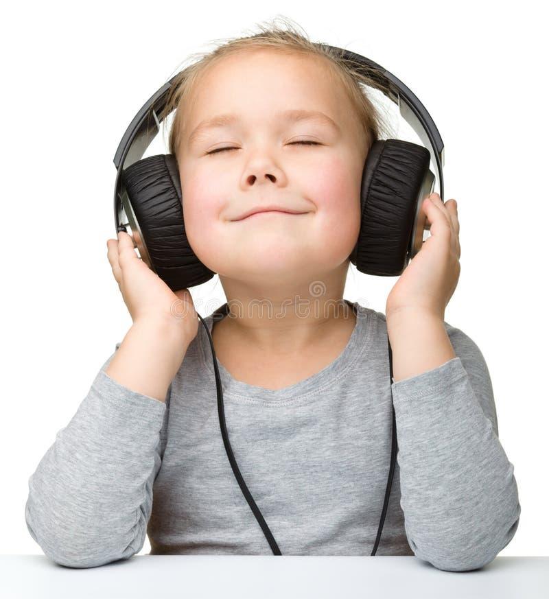 享受音乐的逗人喜爱的女孩使用耳机 免版税库存照片