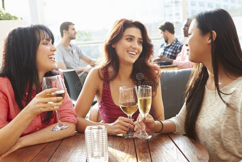 享受饮料的三个女性朋友在室外屋顶酒吧 免版税库存图片