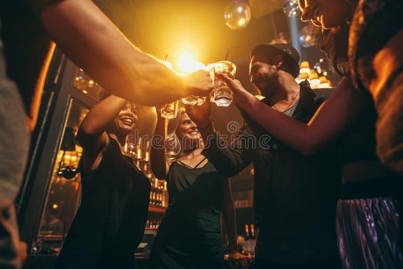 享受饮料的小组朋友在酒吧 免版税图库摄影