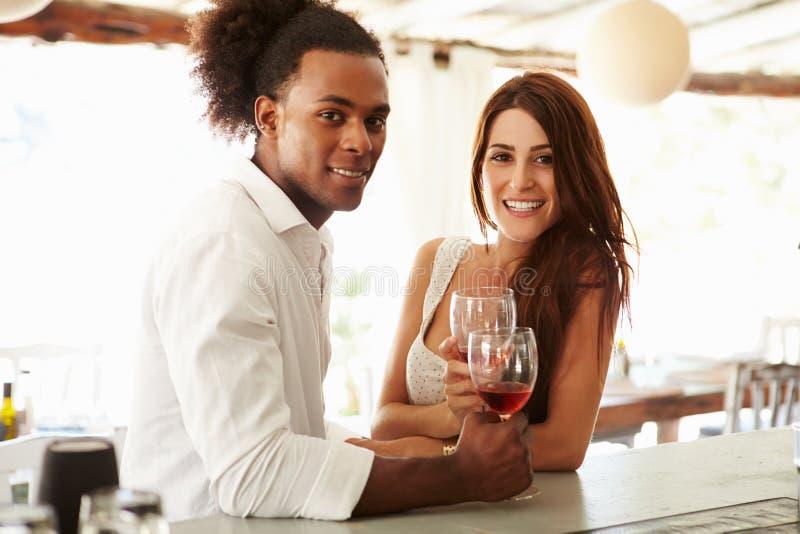 享受饮料的年轻夫妇在室外酒吧 免版税图库摄影