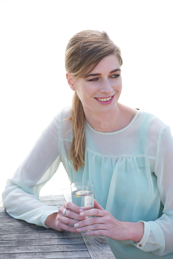 享受饮料a的一个愉快的少妇的画象 免版税库存图片