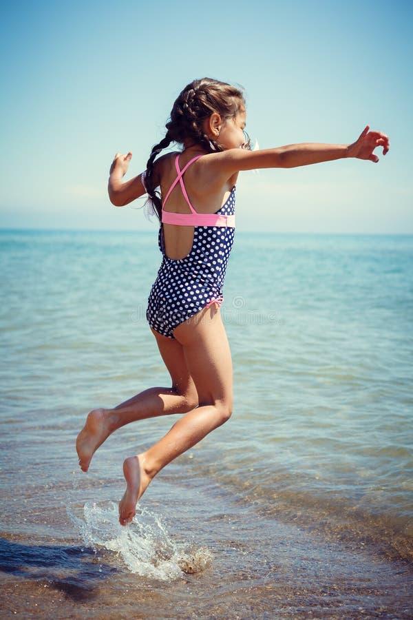 享受晴天的愉快的小女孩在海滩 跳 免版税库存图片