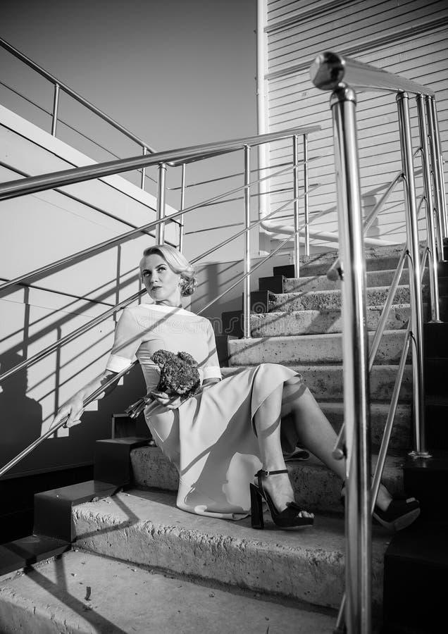 享受 有吹的礼服的时装模特儿妇女在蓝天,户外 新金发碧眼的女人 免版税库存照片