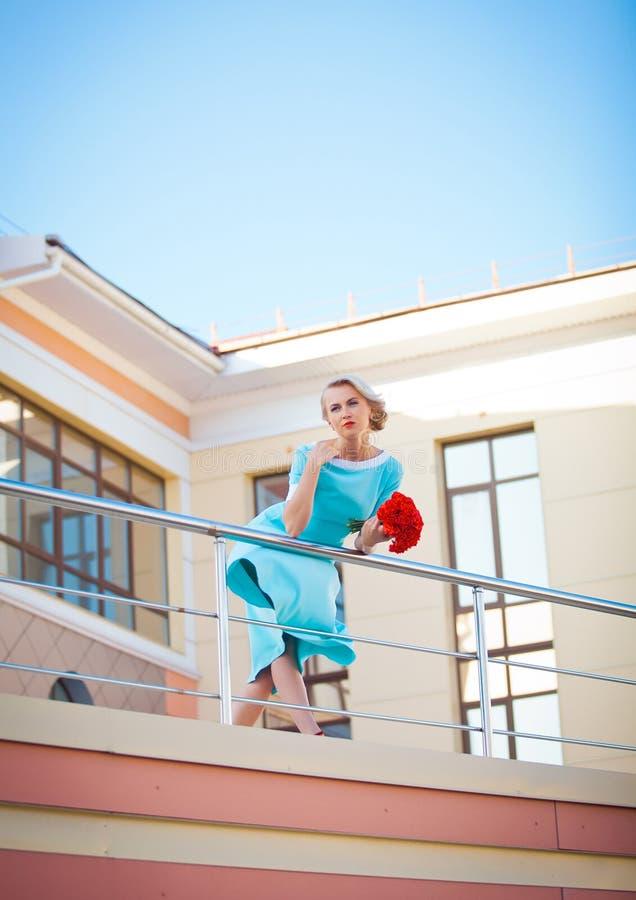 享受 有吹的礼服的时装模特儿妇女 免版税库存照片