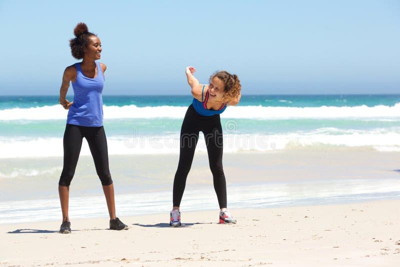 享受锻炼的两个女性朋友在海滩 免版税图库摄影