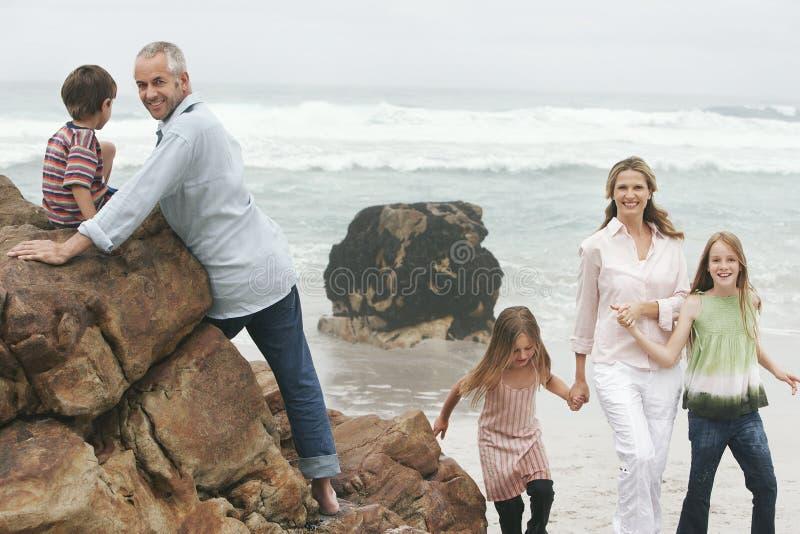 享受他们的假期的家庭在海滩 库存图片