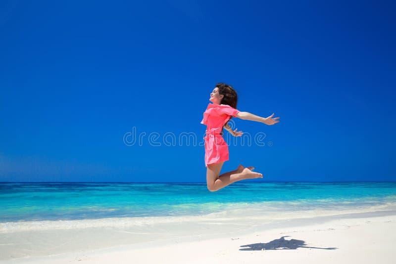 享受 跳过海和蓝天, brune的愉快的自由的妇女 免版税库存照片