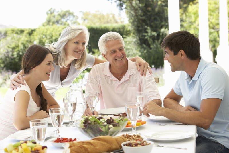 享受Al壁画膳食的父母和成人孩子 库存照片