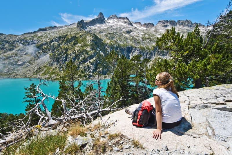 享受Aubert湖和Neouvielle高峰大局的女孩远足者 免版税库存图片