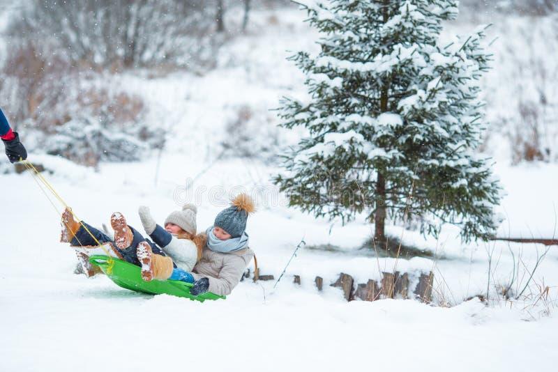 享受sledding的小女孩在冬日 父亲sledding他的小可爱的女儿 家庭度假 免版税库存照片