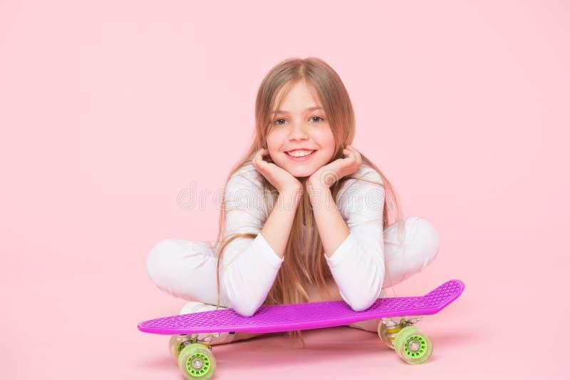 享有在极端速度的生活 放松在桃红色背景的紫罗兰色便士板的愉快的小极端运动员 r 免版税库存图片