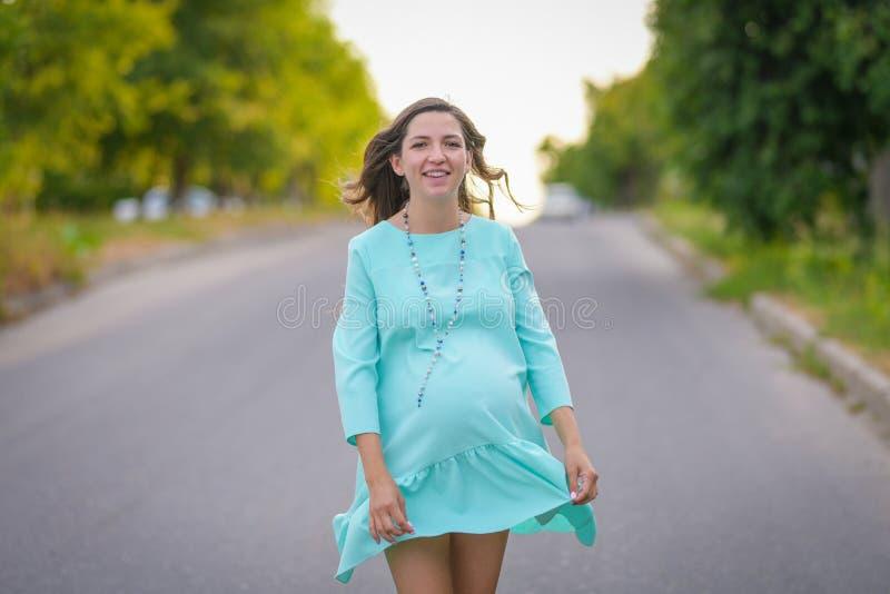 享有生活的年轻孕妇户外在夏天 免版税库存图片