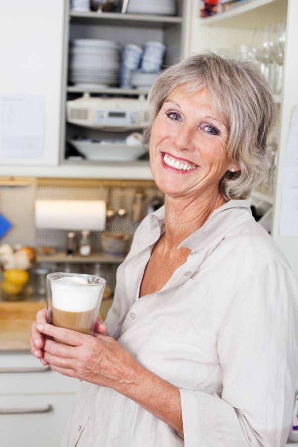 享用一个杯子热奶咖啡的年长妇女 库存图片