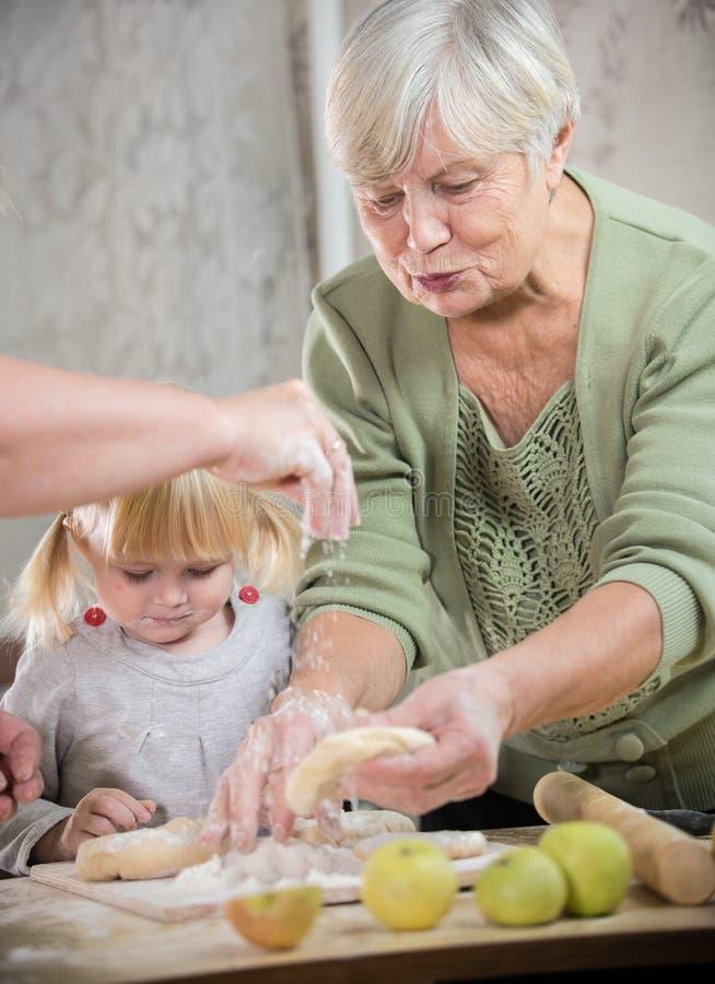 享用一个的老妇人做与她的孙女的小的苹果饼 面团在妇女手上洒与面粉 免版税库存图片