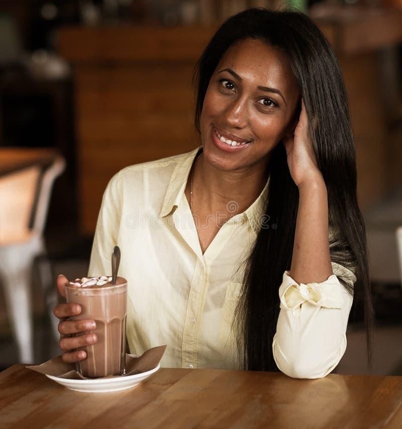 享用一杯咖啡的美丽的年轻非洲妇女 免版税库存图片