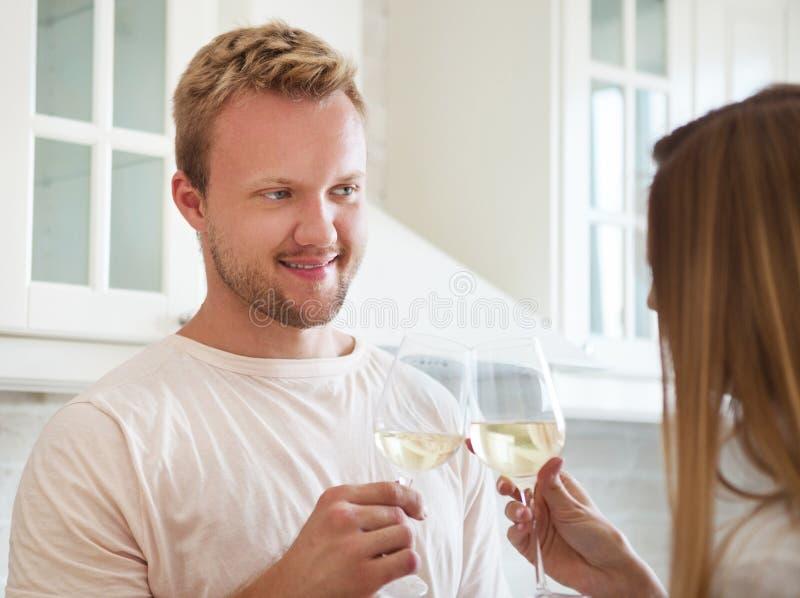享用一杯白葡萄酒的愉快的年轻夫妇 库存图片
