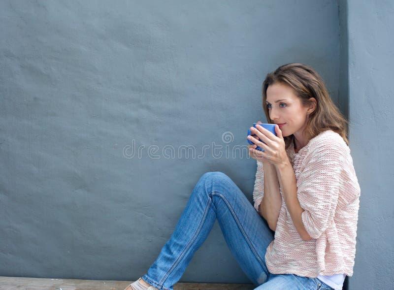 享用一杯茶的可爱的中间妇女 库存照片